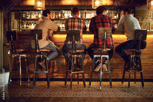 Obraz Rear view friends sitting on chairs talking at the bar in a bar. - fototapety do salonu