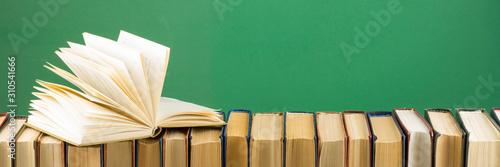 Open book, hardback books on wooden table Wallpaper Mural