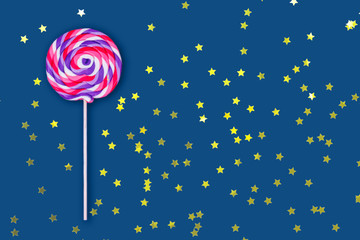 Big lollipop on solid classic blue background. Horizontal with festive golden star shaped confetti