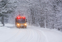 School Bus Travelling On A Snow Covered Rural Road With Stop Lights Flashing
