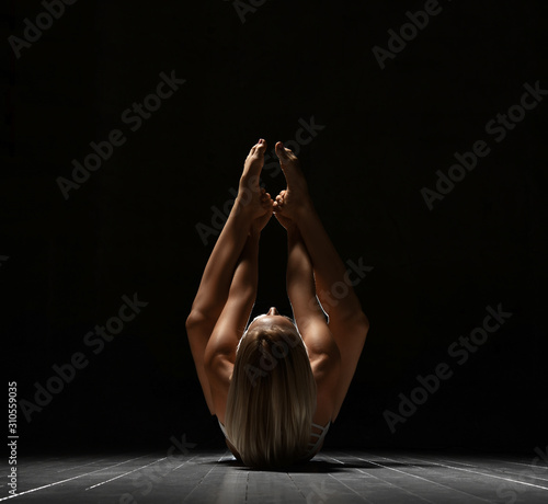 Fotomural  Beautiful athletic girl trainer doing yoga difficult pose stretches in sport fit
