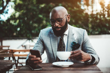 An Elegant Mature Bald Bearded African Man In A Fashionable Costume With A Necktie And Spectacles Is Using One Of His Smartphones While Sitting In A Street Cafe With A Cup Of A Delicious Tea