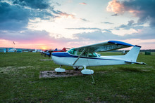 Small Private Aircrafts Parked At The Airfield At Scenic Sunset