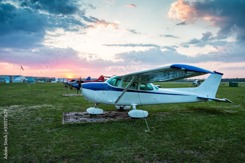 Small private aircrafts parked at the airfield at scenic sunset Canvas Print