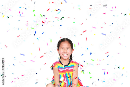Obraz Happy little child girl with colorful confetti on white background. Happy New Year or Congratulation Concept. - fototapety do salonu