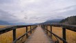 POV walking shot onto wooden pathway / bridge in beautiful winter scene with mountains in distance