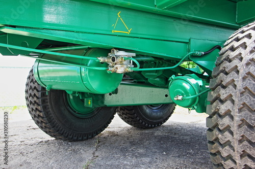 Photo Pneumatic brakes on green tractor trailer frame close up, metal pipeline, distri