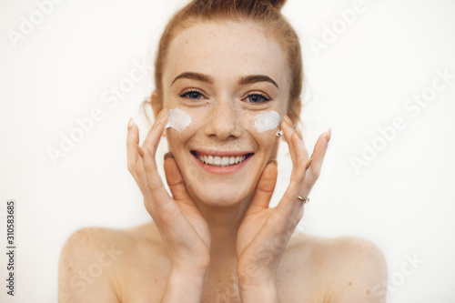 Fotografía  Portrait of a charming young woman looking at camera laughing while playing with both hands cream on her cheeks