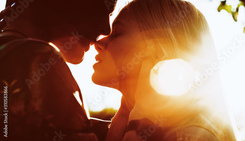 Fotomural Side view portrait of a amazing young couple face to face before kissing against sunset while traveling