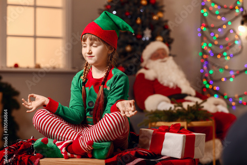Meditating girl in costume of elf in room decorated for Christmas