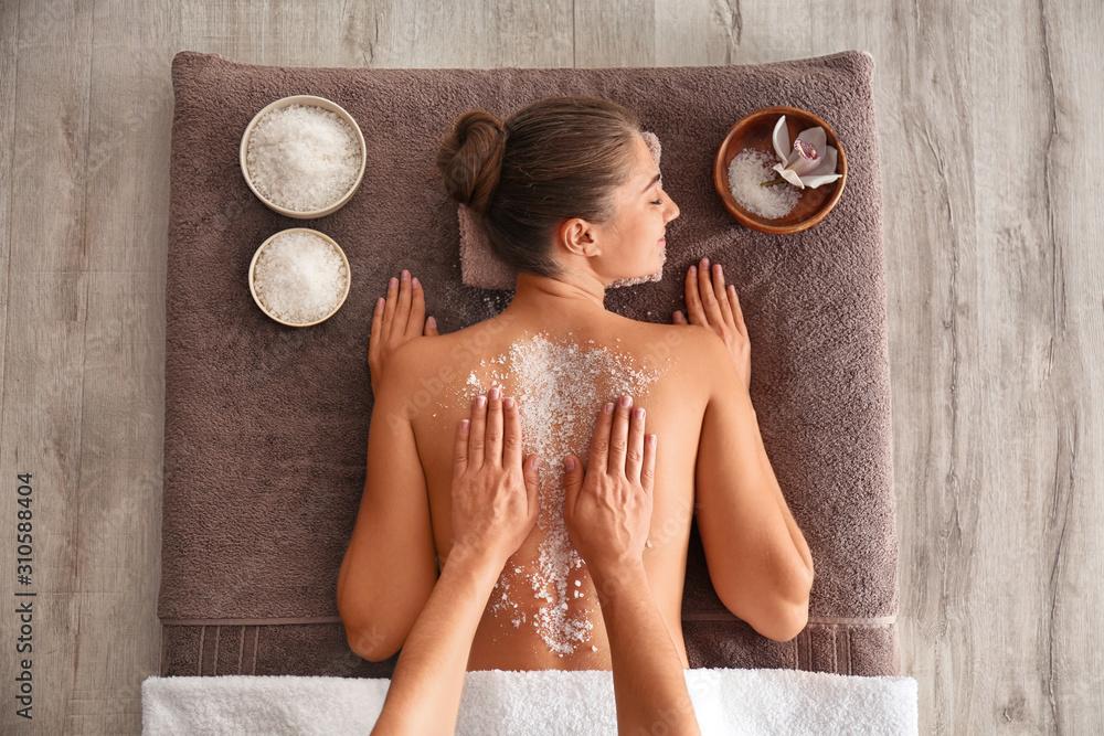 Fototapeta Young woman having body scrubbing procedure with sea salt in spa salon, top view