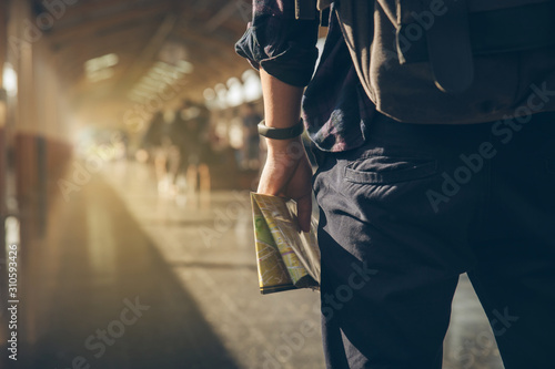 Tourist backpacker holding map standing at train station for travel Canvas Print