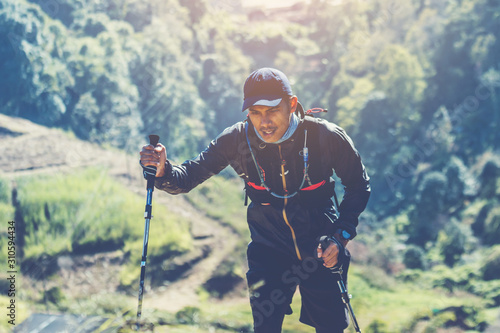 Fototapeta Runners. Young people  trail running on a mountain path. Adventure trail running on a mountain. Athletic attractive people running enjoying the sun exercising their healthy lifestyle. obraz na płótnie