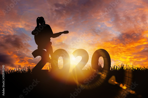 2020 New Year : Young  woman playing guitar and relaxing with music on 2020 New Year,  Happy new year concept - 310595240