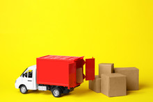 Toy Truck With Boxes On Yellow Background. Logistics And Wholesale Concept
