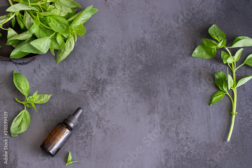 Fresh basil leaves and basil essential oil in a Glass Bottle on dark concrete background Fototapet