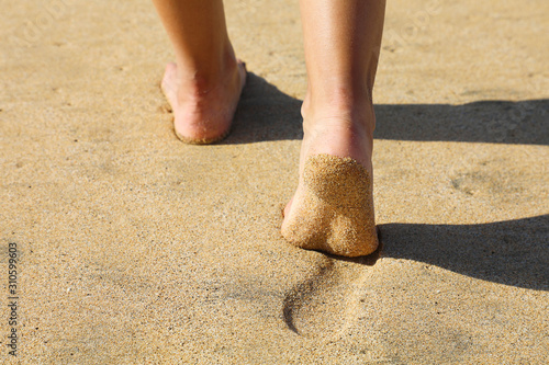 Beach woman legs feet walking barefoot on sand leaving footprints on golden sand in sunset. Vacation travel freedom people relaxing in summer.