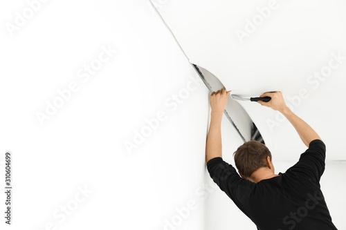 Fotografía  Repairman installing white stretch ceiling in room