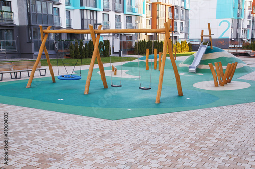 Obraz Public playground for kids in the local area among apartment buildings - fototapety do salonu