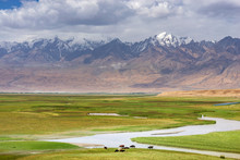 Fresh Green Meadows Of Prairie And Snow-capped Mountain Ranges