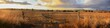 Panoramic views of dry, drought stricken farm land through old steel locked farm gates on a hot afternoon in Gunnedah, New South Wales, rural Australia