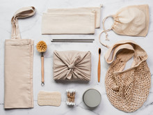Zero Waste Gifts Concept. Textile Wrapping Gift, Eco Bags, Metal Straws, Eco-friendly Kitchen Tools, Bamboo Toothbrush And Cotton Buds, Reusable Cotton Pads On White Marble Background. Top View