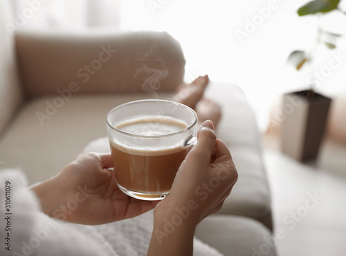 Fototapeta Woman with cup of hot drink on sofa at home in morning, closeup