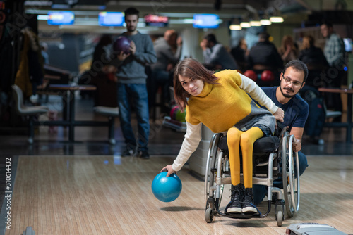 Obraz Disabled woman in a wheelchair bowling - fototapety do salonu