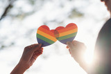Fototapeta Tęcza - Close up hand of LGBTQ couple holding rainbow heart.