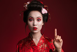 Image of asian geisha woman in japanese kimono pointing finger upward