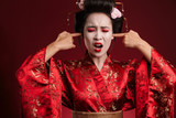 Image of geisha woman in japanese kimono plugging her ears with fingers