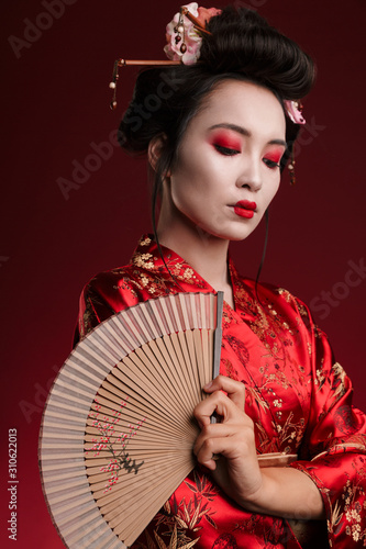 Canvas-taulu Image of young geisha woman in japanese kimono holding wooden hand fan