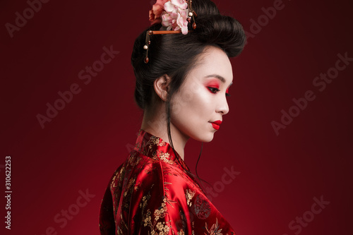 Fotografie, Tablou Image of charming geisha woman in japanese kimono looking downward