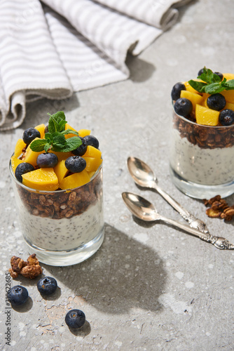 selective focus of fresh granola with canned peach, blueberries and chia seeds on grey concrete surface with spoons, mint and napkin - 310622685