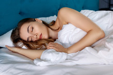 Young Beautiful Woman Sleeping In Cozy Bed In The Bedroom.