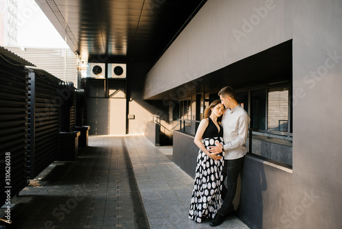 Obraz The parents are walking around the city, cuddling and enjoying the anticipation of your baby - fototapety do salonu