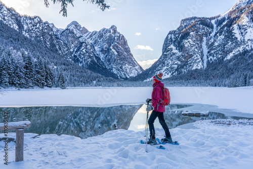 nice senior woman snowshoeing on a cold winter morning on the shore of Lago Dobb Tablou Canvas