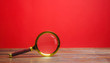 Magnifying glass on a red background. Search and analysis, analytics and study. Pay attention to details and problems. Find something. Journalistic investigations and research. Search tool