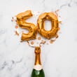 canvas print picture - Champagne bottle with gold number 50 balloon. Minimal party anniversary concept