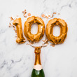 canvas print picture - Champagne bottle with gold number 100 balloon. Minimal party anniversary concept