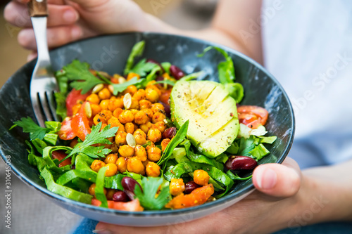 Fotografia Clean eating, vegan healthy salad bowl closeup , woman holding salad bowl, plant