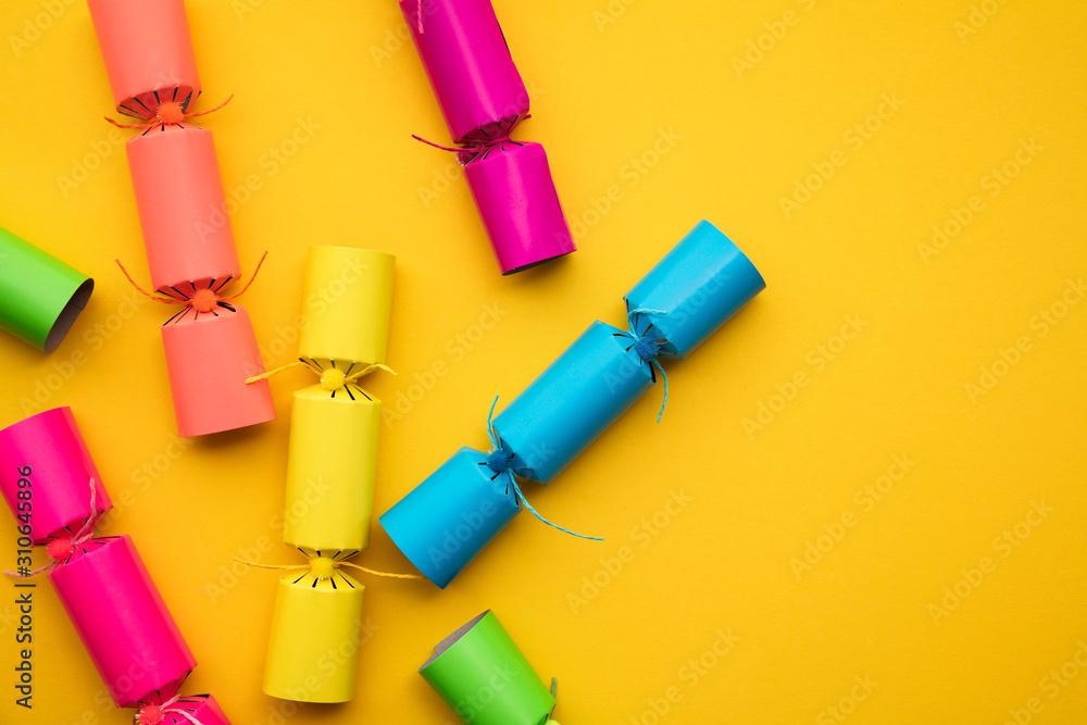 Fototapeta Bright colourful Christmas crackers on a yellow background. festive layflat