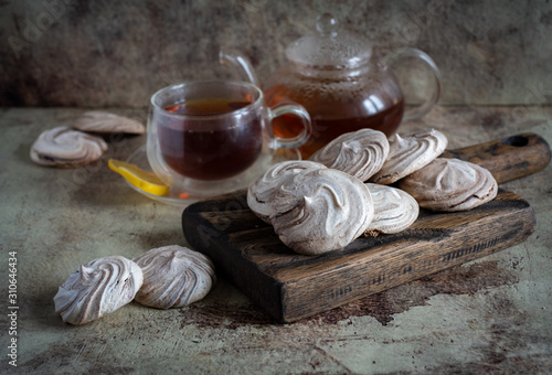 Fotomural  Chocolate dessert: meringues with chocolate on a wooden Board and a Cup of teaCh