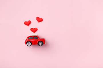 Red retro toy red car with red bow for Valentine's day on pink background with heart confetti. Top view, flat lay