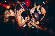 Female Friends Drinking Wine And Celebrating New Year At The Club