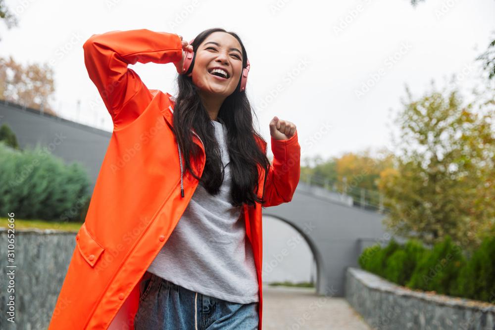 Fototapeta Smiling young asian woman wearing raincoat walking outdoors