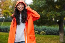Smiling Young Asian Woman Wearing Raincoat Walking Outdoors