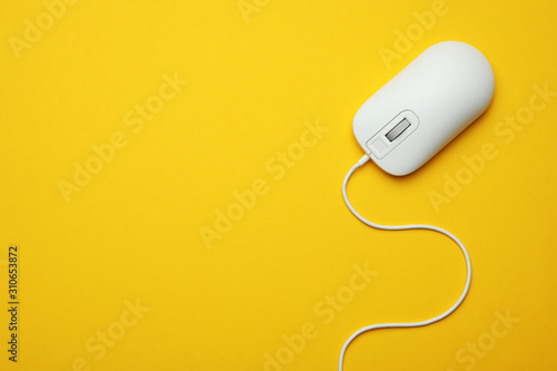 Fototapeta Wired computer mouse on yellow background, top view