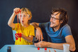 Leinwanddruck Bild - Father and son conduct chemical experiments at home. Home made slime. Family plays with a slime