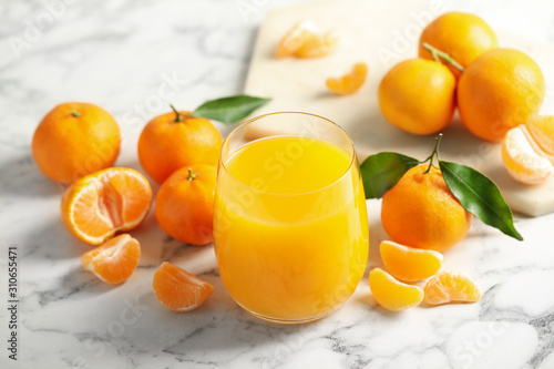 Obraz Glass of fresh tangerine juice and fruits on marble table - fototapety do salonu